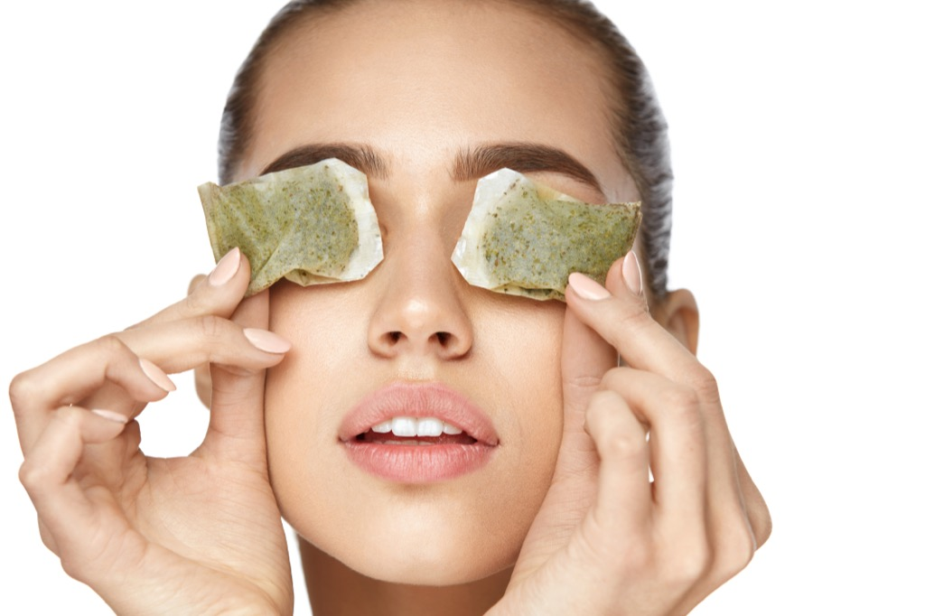 a woman putting chilled green tea bags on her eyes