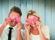 Man and woman holding cardboard cutouts over eyes