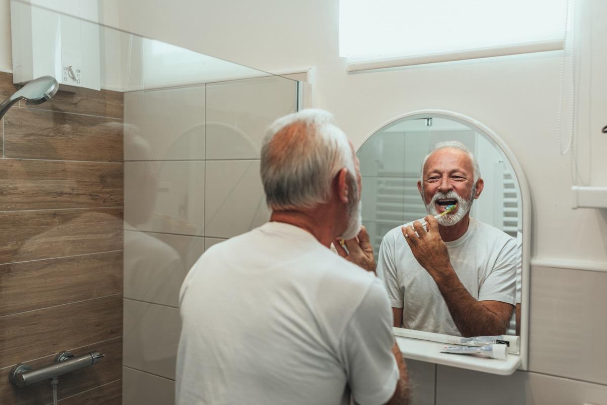 Older man brushes teeth in mirror, things damaging teeth