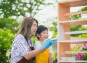 Asian mom and son paint shelf outside