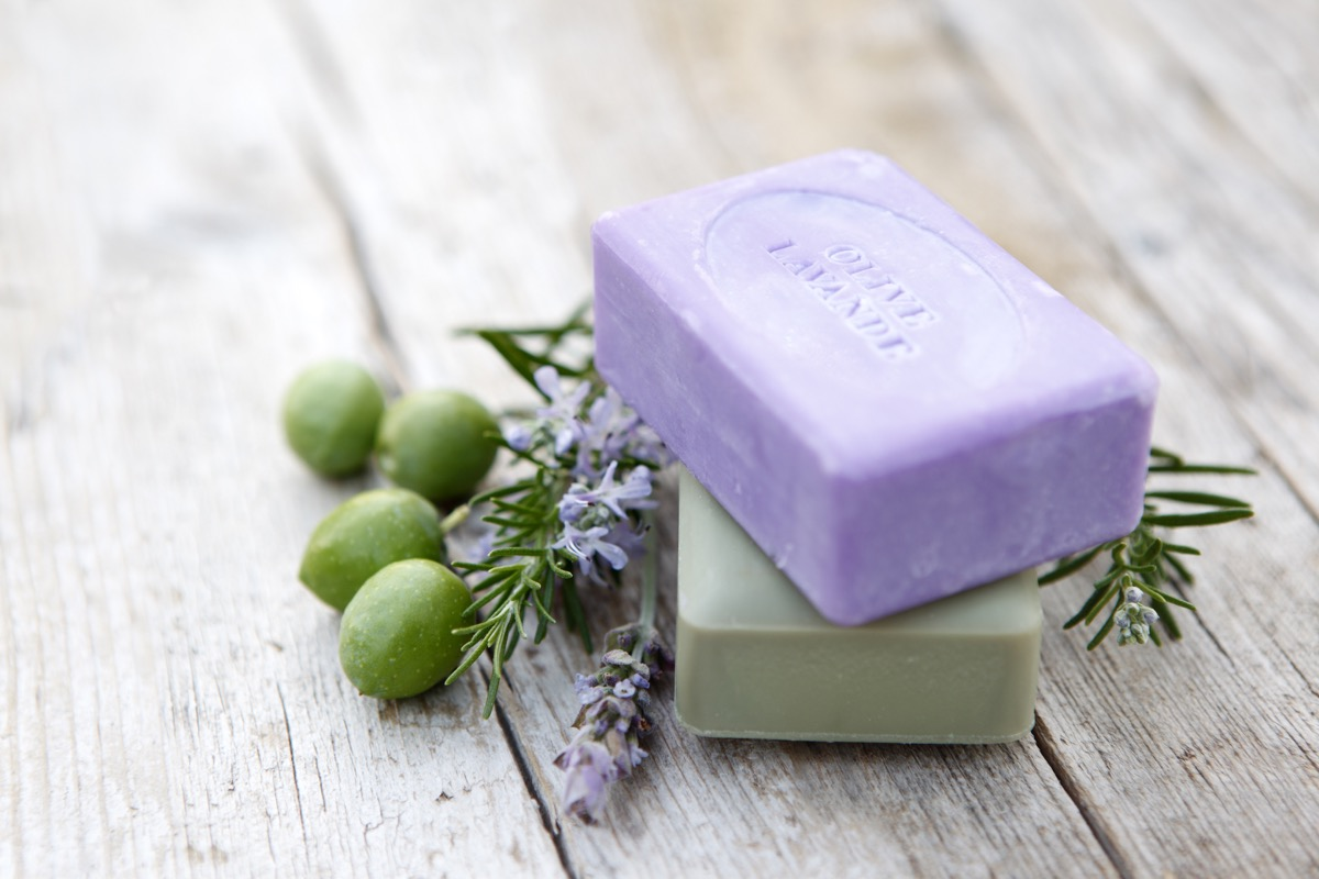 Bars of coloured handmade soaps with herbs and olives.