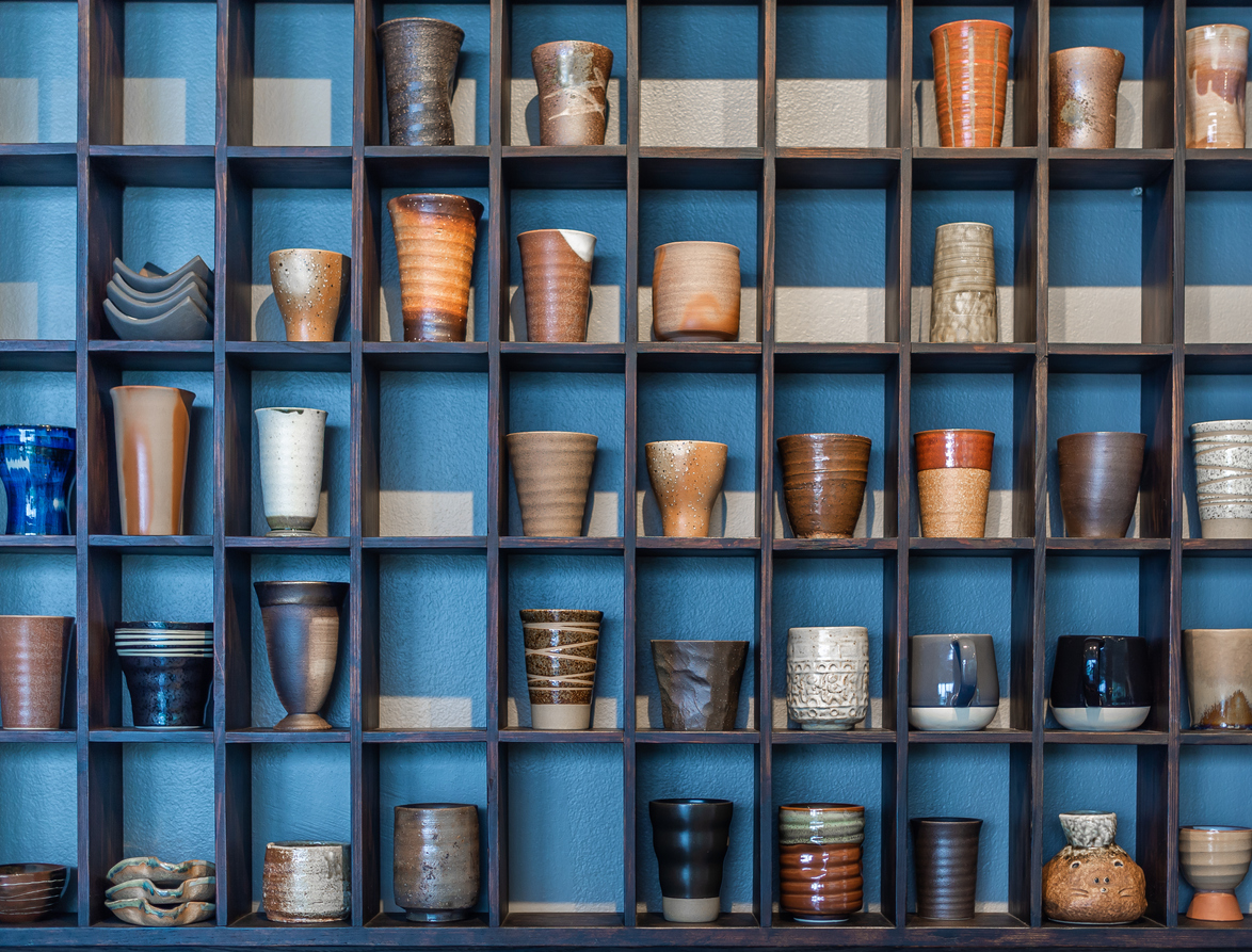 Various and colorful ceramic mugs on modern wooden shelf on blue background.