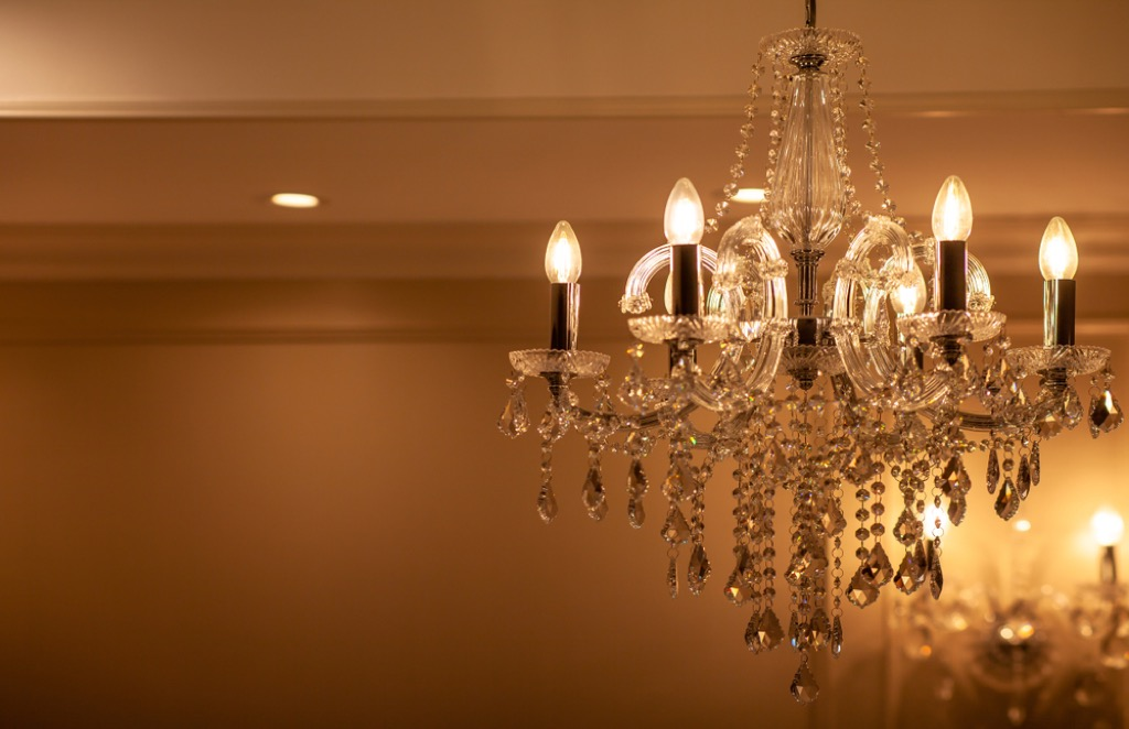small crystal chandelier in dimly lit room with overhead can lighting