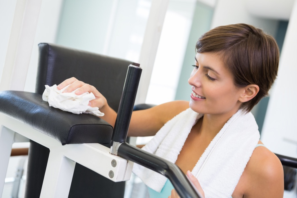 woman cleaning gym equipment