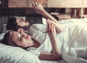 bored couple lying in bed with smartphones, things you should never say to your spouse