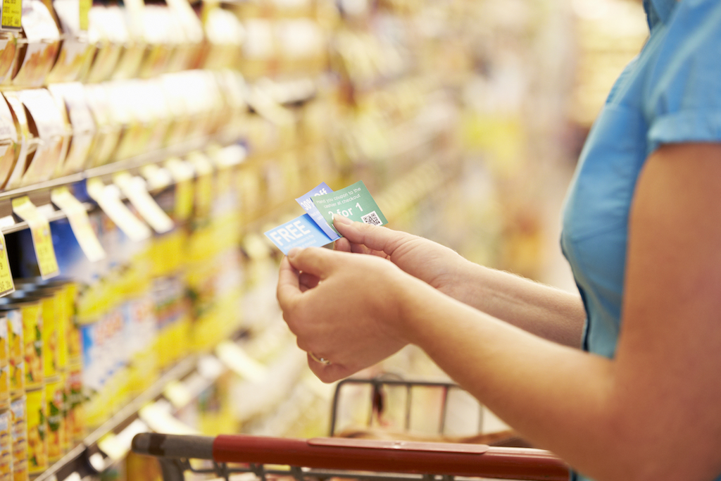 woman in grocery store looking at collection of coupons