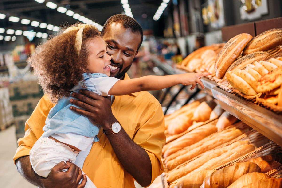 dad and daughter looking at bread in the grocery store
