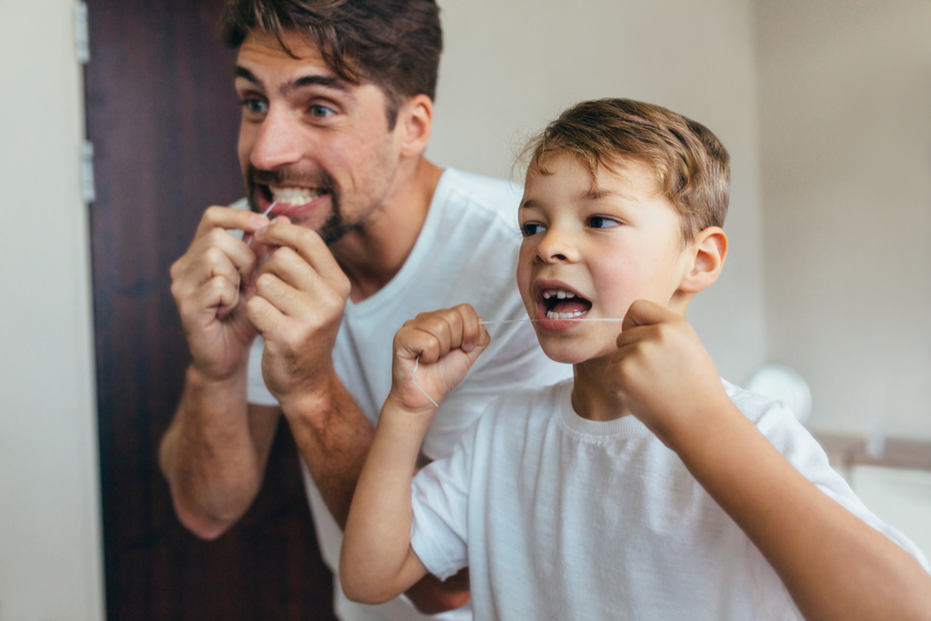 dad and son flossing teeth, how parenting has changed