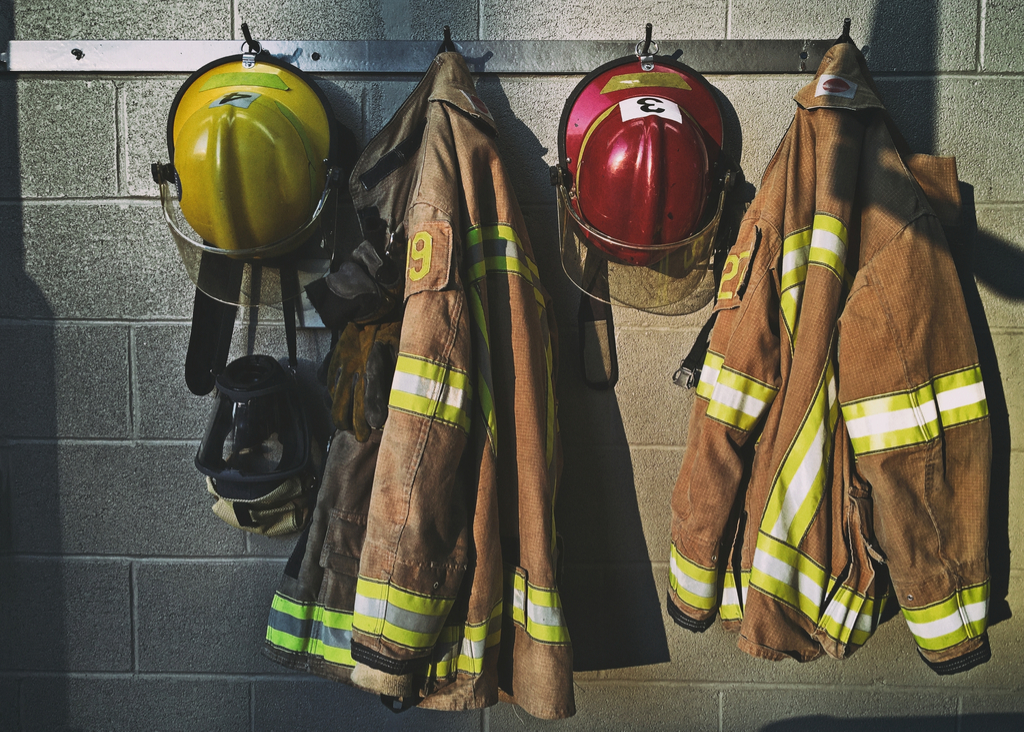 firefighters uniforms hanging on hooks at fire house