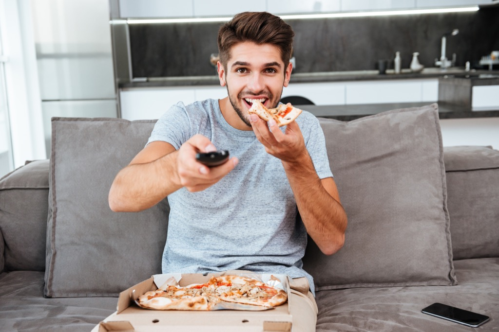 man eating food in front of the television
