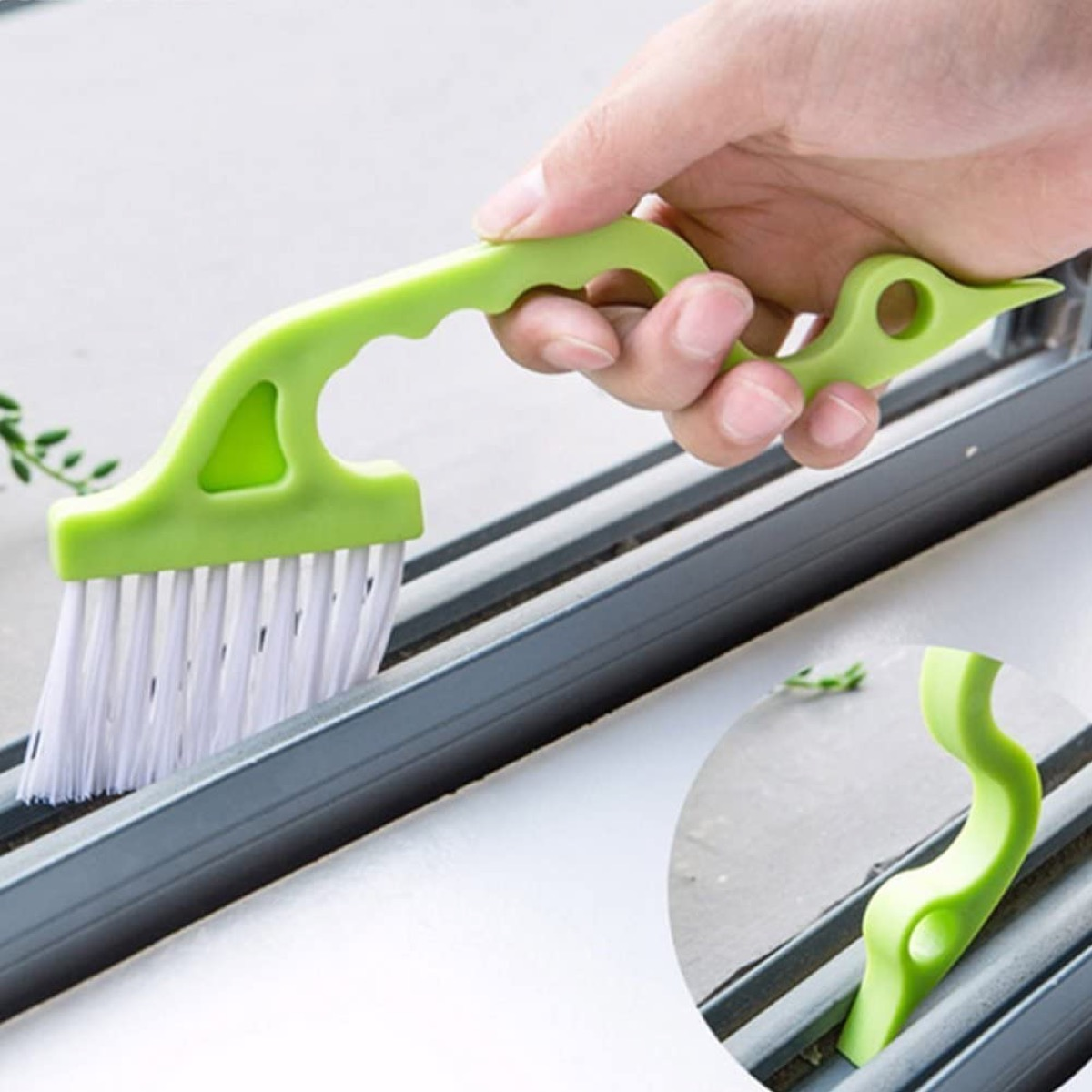 white hand cleaning window gap with green brush