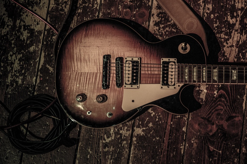 vintage gibson les paul on a beat up wooden stage