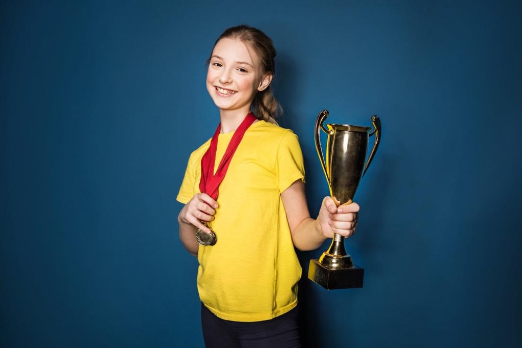 girl holding medal