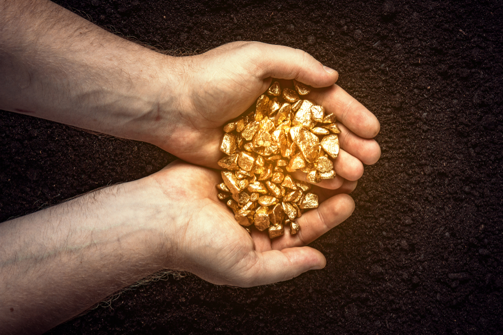 man holding gold nuggets