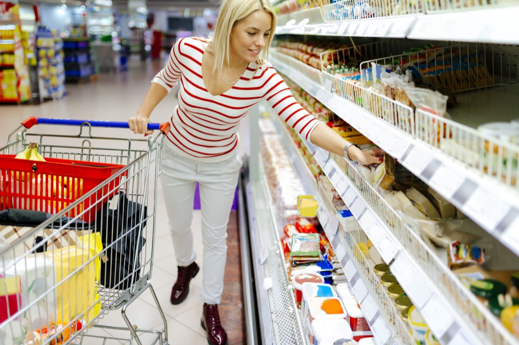 woman picks up milk at grocery store