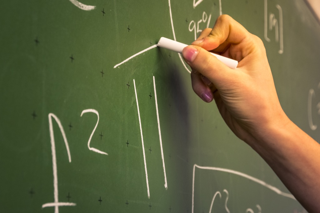 a hand writing out 6th grade math equations on a chalkboard {Tricky Math Questions}
