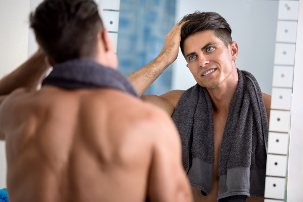 handsome man with towel around shoulder looking into mirror