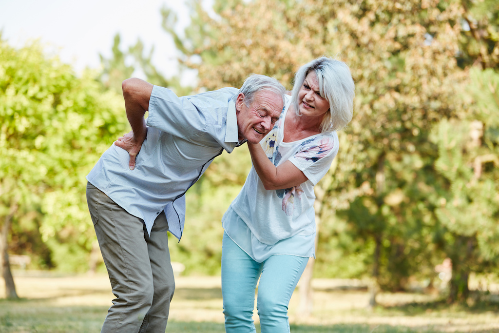 old man suffering from hip and lower back pain getting assistance