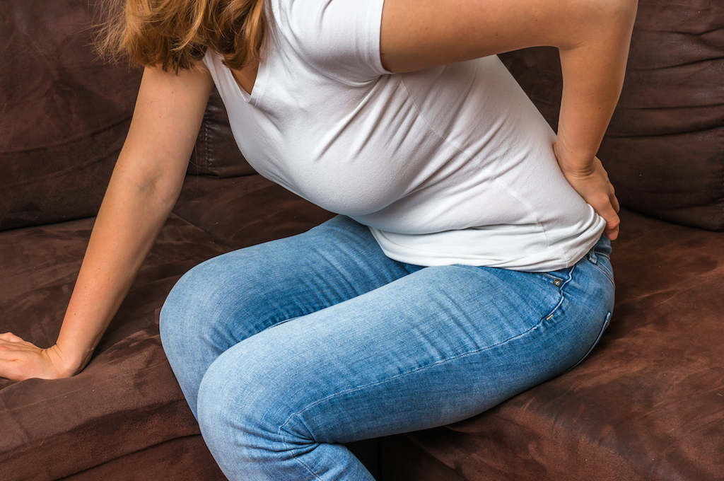 woman bent over on the couch with hip/back pain
