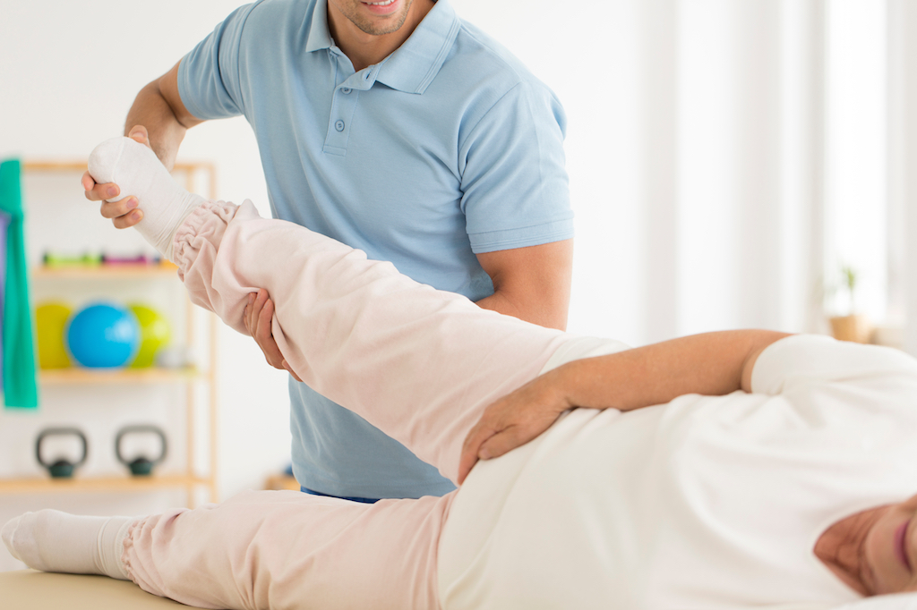 older woman getting her hip stretched out, female health concerns after 40