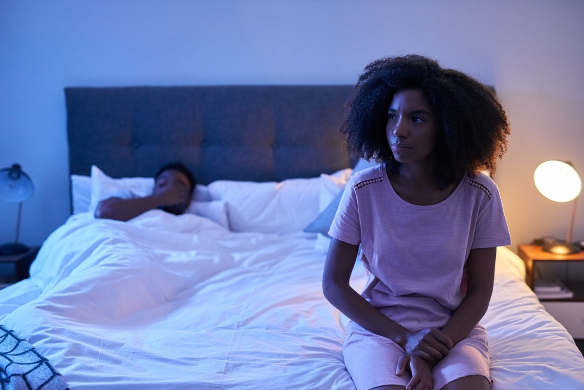 young black woman sitting up worried in bed with partner in the background