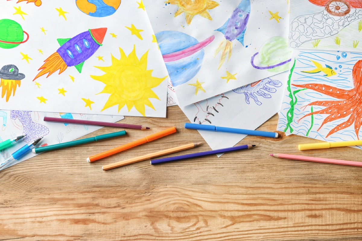 children's art and colored pencils on wooden desk, home upgrades