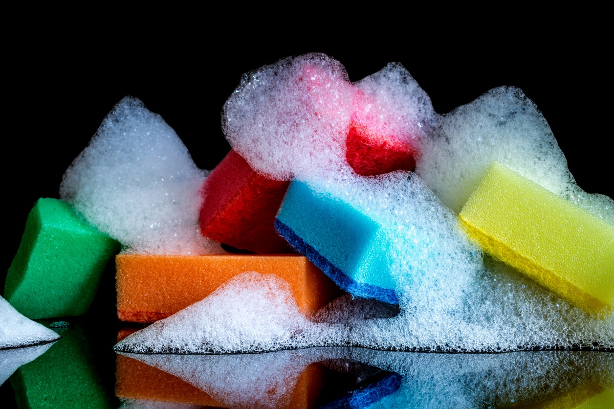 Colorful sponges with foam and reflection isolated on black background