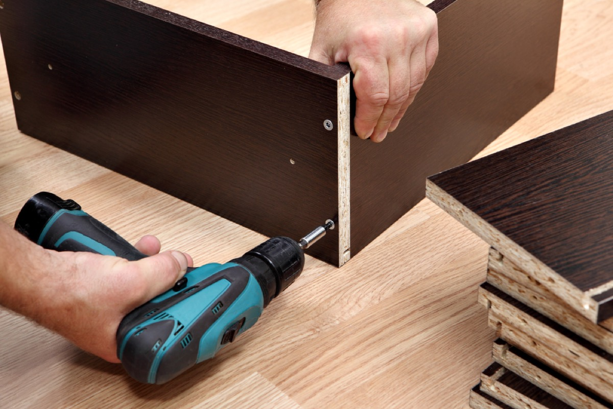 man drilling together black particleboard furniture, home upgrades