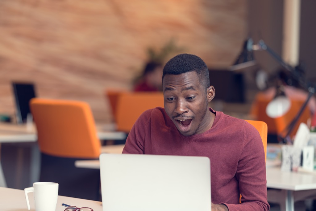 man looking astonished at a laptop