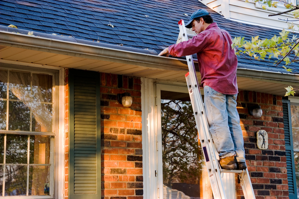 Man Cleaning Out Gutters Boosting Your Home's Curb Appeal
