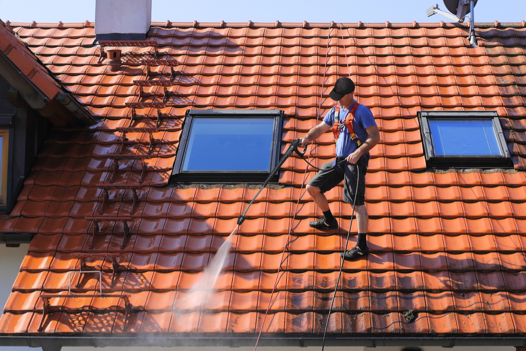 Man Cleaning Roof Boosting Your Home's Curb Appeal