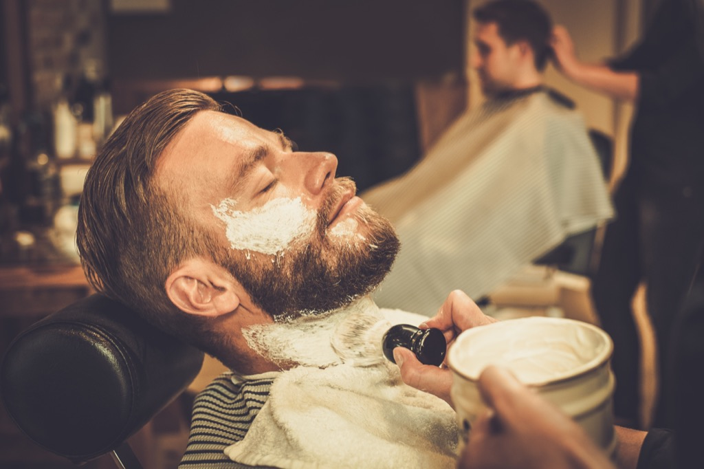 man getting a shave from a barber