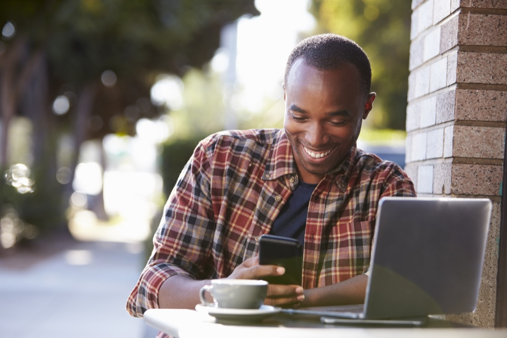 Man sitting outside at coffeeshop using phone and laptop