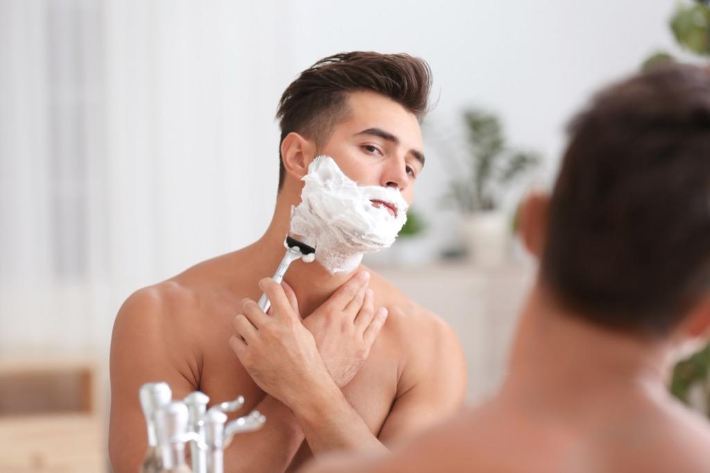 man shaving off shaving cream in front of a mirror