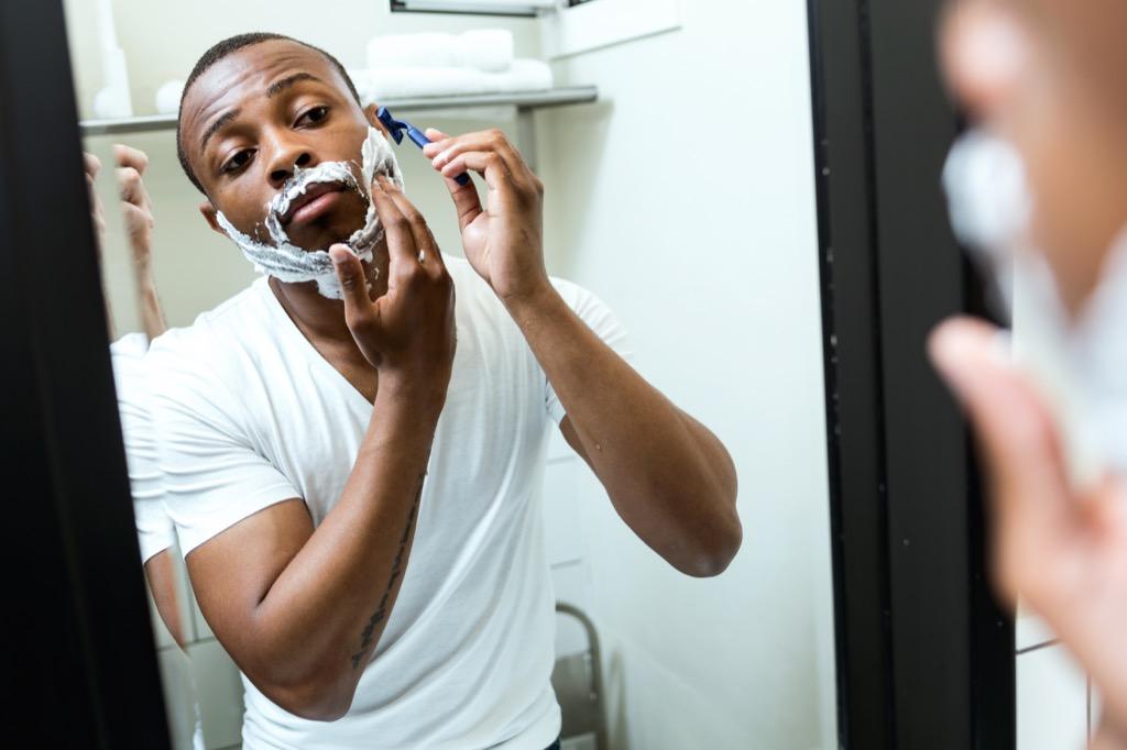 black man shaving in the mirror