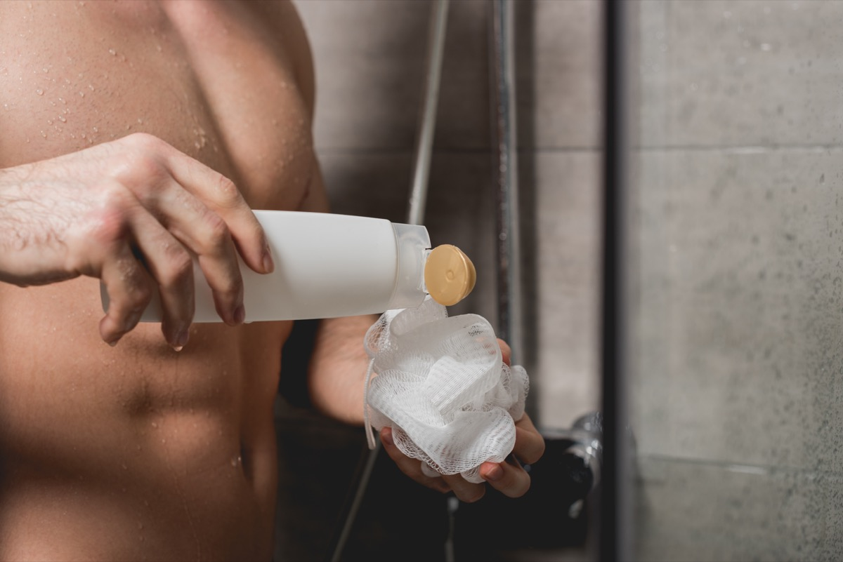 Man using a loofah in the shower