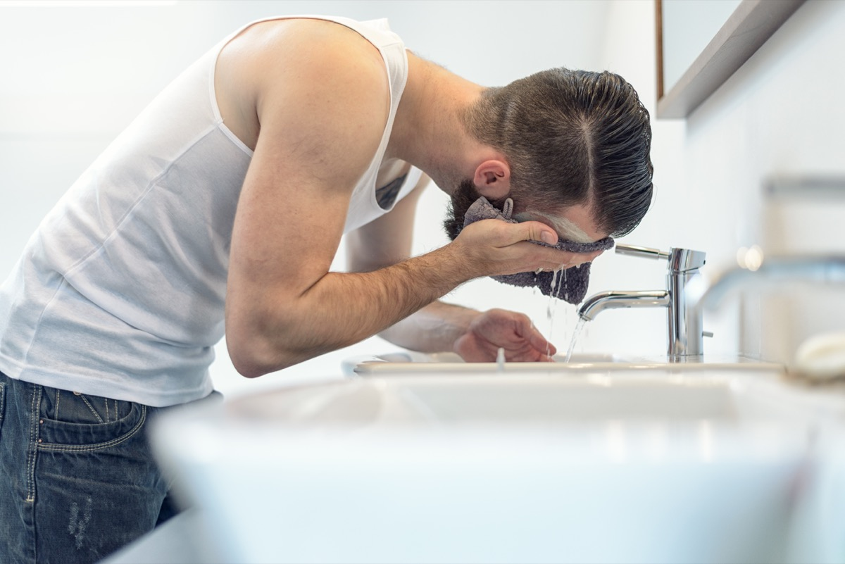 Man washing his face with a washcloth