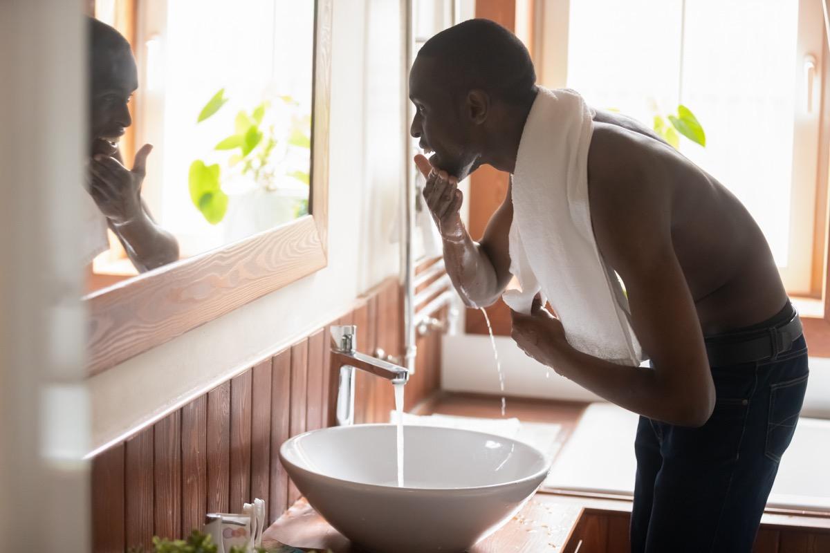 Man washing face at sink