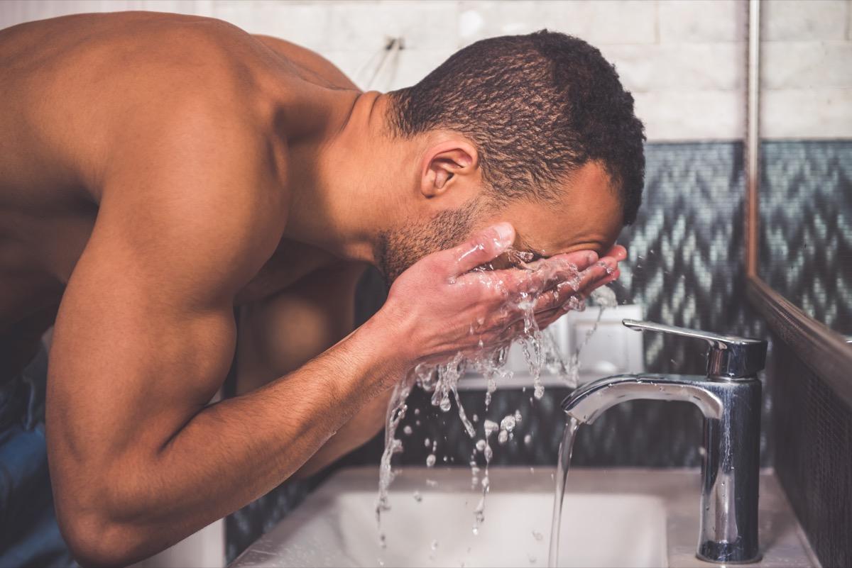 Man splashing his face with water at sink
