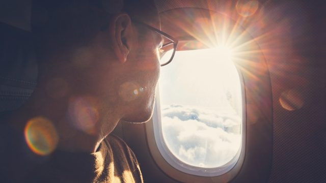 man in glasses looks out an airplane window