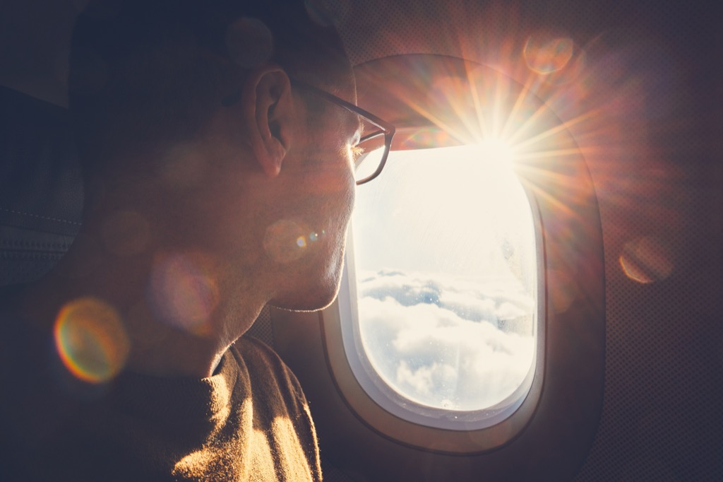 man wearing glasses looking out airplane window