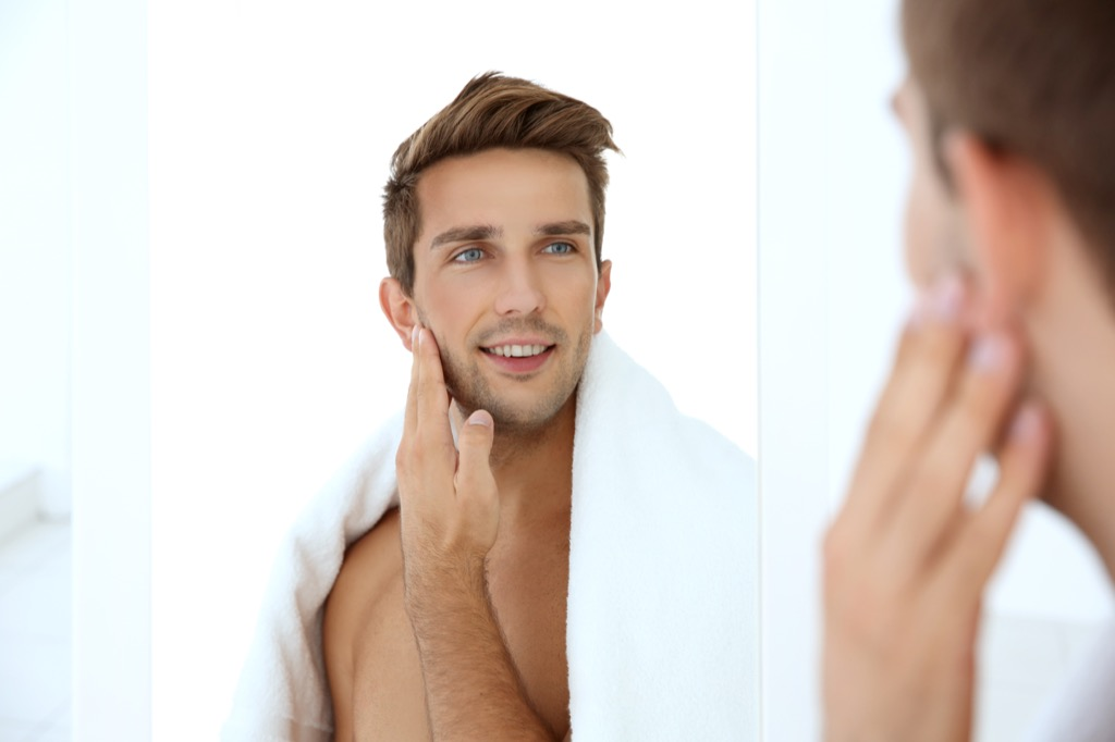 man with a towel looking at himself in the mirror