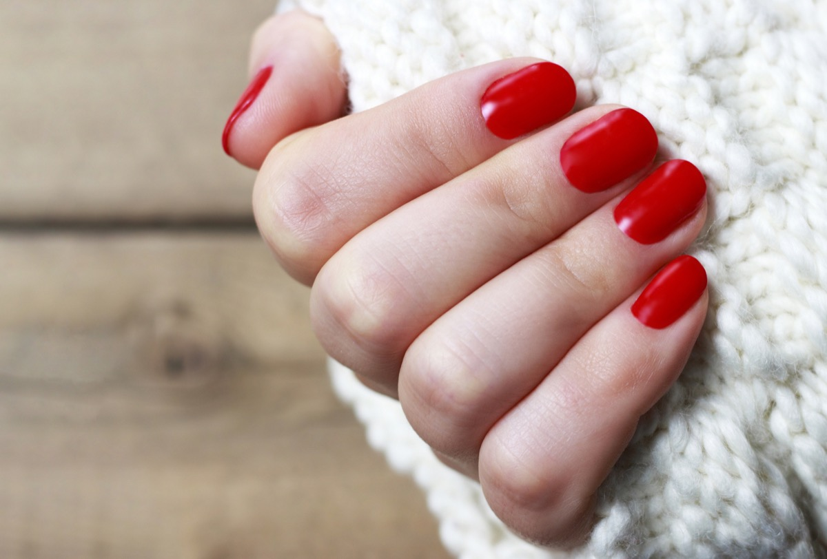 Female hand with red manicure on a white knitted background with copy space, top view