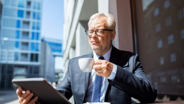 an older businessman ponders retirement while looking at an ipad, office etiquette