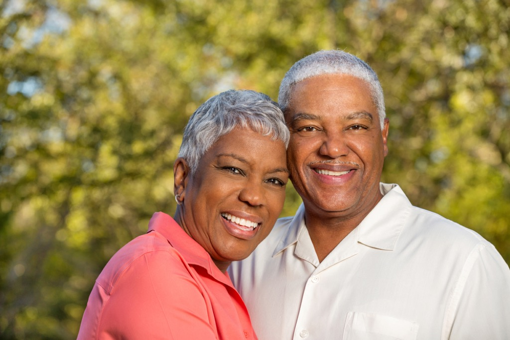 older couple smiling outside Signs Your Hair Will Go Gray