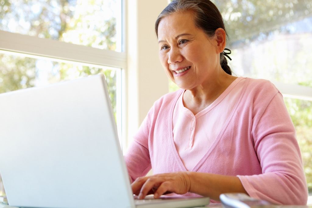 older woman on computer, learning a language is good for your brain