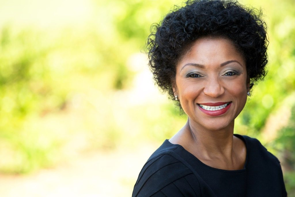 older woman smiling outside, look better after 40