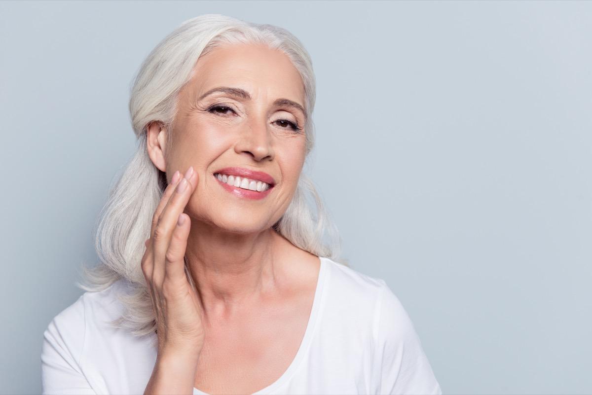 Older woman touching skin