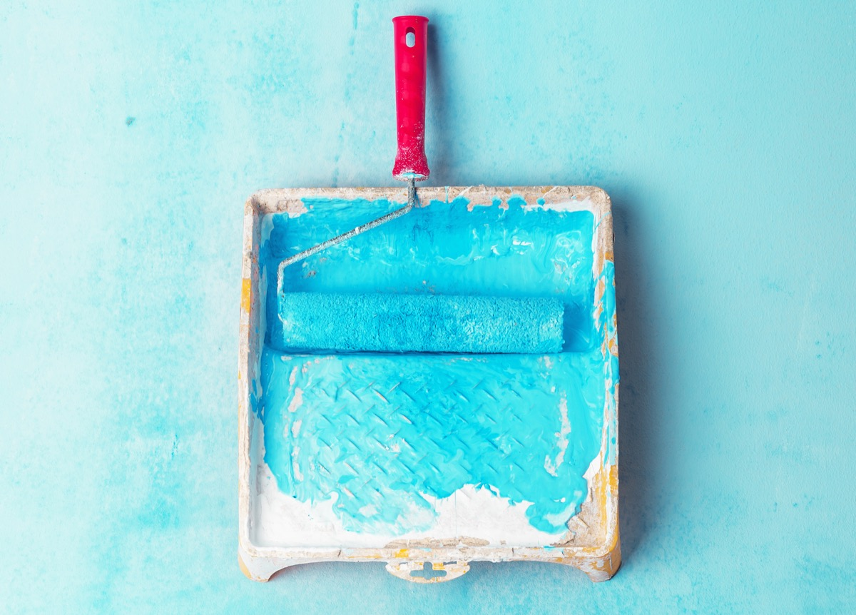 Tray paint and paint roller color light blue. Creative background