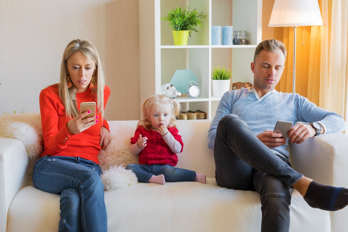 mom and dad sitting on a white couch playing with cell phones in front of their young daughter, prepare children for divorce